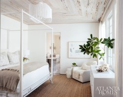 """One of two master bedrooms, this upstairs master suite is tucked away in what is """"essentially its own wing,"""" Turner says. A pecky cypress ceiling provides texture, as do a Made Goods chandelier and Surya rug. The armchair is through Bungalow Classic."""