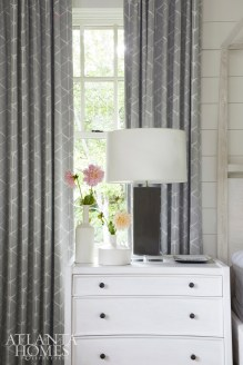 A four-poster bed made of reclaimed wood with a whitewash finish by Noir Furniture from JDouglas Atlanta takes advantage of the high ceilings in the youngest daughter's bedroom. Atop an end table from Noir Furniture, a lamp from Bungalow Classic complements the patterned linen drapery from Romo.