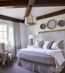 A bed from Hickory Chair with a linen slipcovered headboard by Pindler and a printed linen bed skirt by Carolina Irving Textiles fosters a relaxing atmosphere in the lower-level guest suite.
