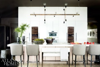 Poggenpohl cabinetry anchors the luminous kitchen, while a dazzling Coup Studio light fixture from R Hughes hovers above. A mix of stool and bench counter seating breaks up the expansive space.