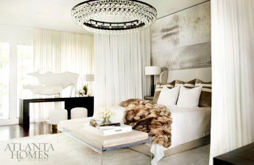 In the master bedroom, with its billowing curtains, walls swathed in hide and a floating mirror, an Ochre chandelier from R Hughes adds another note of glamour. The custom ottoman is by Pfeifer Studio. French animal sculptures, South of Market.