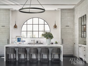 Driftwood adds warmth to the kitchen's edited aesthetic. The stools are by Palecek and the cage light fixtures are from Lumens.