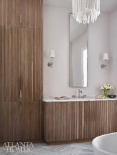 The spa-like master bath combines clean lines and natural materials. The whitewashed light pendant is by Arteriors.