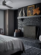 The master bedroom is enveloped in a custom gray flannel curtain wall, alongside rich textures. All windows feature triple-lined blackout curtains for sleeping in. The painting is by Hal Schwarze and the rug is Moattar.