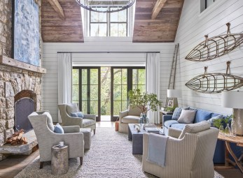Designer Courtney Giles maximized seating in the airy two-story living room with tailored pieces from Bungalow Classic. A custom painting by artist Blayne Macauley captures the living room's dusky blue palette, while a pair of canoe maquettes suspended from the wall with rope play up the home's escapist appeal.