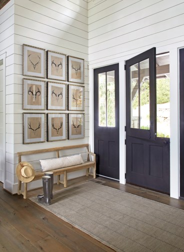 A collection of deer and elk skull prints purchased at Scott Antique Markets graces the front entry. The antique bench is from Foxgloves Antiques.