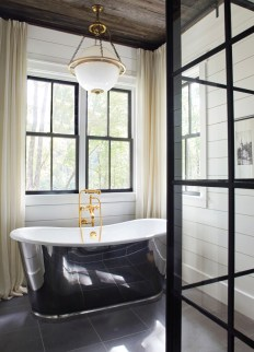 The spa-like master bath features an eye-catching steel-and-glass shower enclosure and a soaking tub with prime views overlooking the scenic backyard.