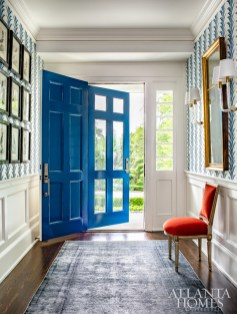 In the foyer, a Carleton V's Gatsby wallcovering, sourced through Ainsworth-Noah, echoes the front door's vibrant blue hue, which Kleinhelter used as the jumping point for the home's color story.