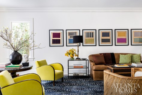 In the living room, chartreuse Deco chairs make a statement, playing off colorful French fabric pieces that were framed and mounted on the back wall.