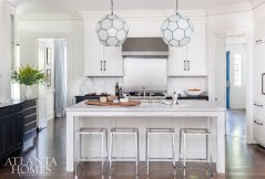 """The kitchen is """"headquarters of the house,"""" Kleinhelter says, so it needed to be both functional and streamlined. She eliminated ornate hardware on some of the room's nonfunctioning cabinetry, painting lower cabinets Benjamin Moore's Polo Blue to tie in with the rest of the home. The light fixtures are through Pieces."""