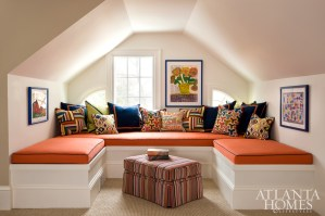 The home's attic is reimagined as a colorful media room; children's artwork and pillows from Jonathan Adler adorn the space.