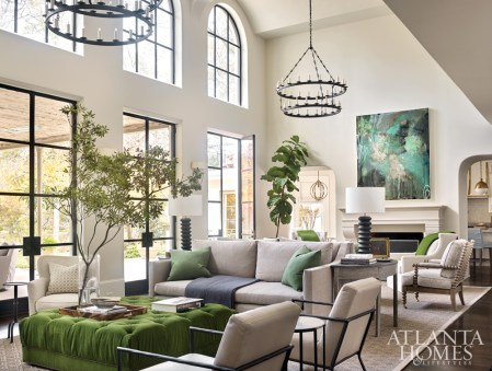 Back-to-back sofas made by Douglass Workroom create two distinct sitting areas. The spindle chairs are Hickory Chair, the custom tufted ottoman is by Bjork Studio and the chandeliers are by Paul Ferrante through Ainsworth-Noah.