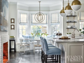 Detailed with tape trim, the roman shades in a Holland & Sherry fabric are one of many blue accents in the kitchen, which was renovated for the previous homeowners with Amanda Orr Architects. The tile is Walker Zanger and the brass globe pendants are Circa Lighting. The artwork by Kristin Blakeney is from Gregg Irby Gallery.