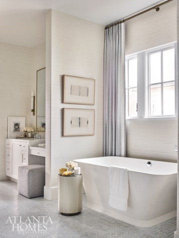 The master bathroom benefits from a curated collection of art, such as works by Gary Gessler, which hang next to the tub, which is from Ferguson.