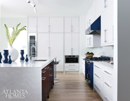 Thermofoil cabinets and a blue Viking Tuscany range and hood energize the kitchen. A floating peninsula on one end of the island adds a tablelike setup.