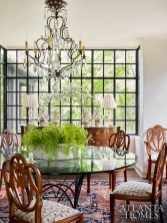 Natural light flows into the dining room from a boxed bay window added during the renovation. The custom iron table is by Smith Ironworks, the chandelier is from Jane Marsden Antiques and the lamps are from Edgar-Reeves.