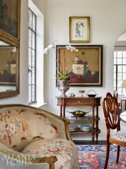 In the dining room, a carved French settee is covered in an Aubusson tapestry. A bright Oriental rug stands out against the newly stained floors. The antique gallery table is from William Word Fine Antiques; the still life is by David Arms from Tew Galleries.