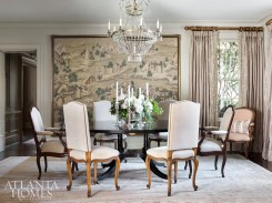 An oversize Gracie wallpaper mural and an early 19th-century chandelier from Robuck set the stage for elegant meals in the dining room. The table is from Holland MacRae and the curtains feature a silk embroidered fabric by Chelsea Textiles.