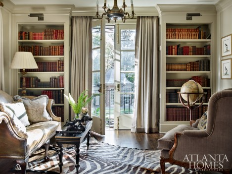 Existing bookshelves in the library were dressed up with molding and other detailing to match the sophistication of the couple's leather book collection. Bryan reupholstered the wing chair and brought in the leather settee that was once located in the dining room.