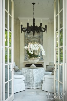 Inspired by a photo of boiserie in an old French château, Bryan commissioned The Finishing Source to repaint the client's existing trumeau mirror. Unique accents such as a limewashed chandelier by Koektrommel adds to the folly's worldly appeal.