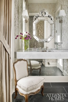 A wall of antiqued mirror reflects the Romo wallcovering in the powder room and creates an elegant backdrop for a floating marble vanity, a Venetian glass-framed mirror and sconces from The Urban Electric Co.