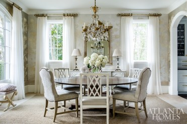"In the dining room, Susan Bozeman selected a Gracie wallpaper for its silver, lavender and pink tones; it creates an ethereal backdrop for a mix of dining chairs from Edward Ferrell and Hickory White. To ""bring down"" the room's formal elements, the designer grounded the space with a sisal rug and sheer curtains."