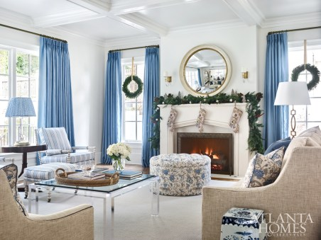 Blue linen draperies by Fabricut enliven the white walls in the living area, where a sofa and love seat from Wesley Hall surround a custom limestone mantel from Materials Marketing. The bespoke fireplace screen is Lucy Smith from Holland MacRae.