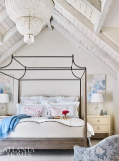 Vaulted ceilings dressed in whitewashed wood planks add drama to the master bedroom.