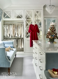 As requested by the owner, the master closet is spacious enough for a quartz-topped center island and a velvet sofa from Wesley Hall. The wallcovering is by Thibaut, and the roman shade is by Larsen Fabrics.