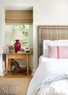 A guest bedroom reveals a menswear attitude with a plaid upholstered headboard and simple wooden table with roman shades. Stronger color comes from a pillow in a Fermoie fabric through Jerry Pair.