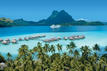 A Paul Gauguin ship amid the overwater bungalows and lush tropical slopes in Bora Bora.
