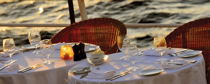 Sunset dining at Candles Grill, Windstar's signature outdoor restaurant which transforms into a moonlit paradise by night.