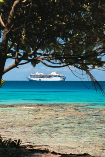 A Paul Gauguin ship is visible through lush tropical foliage of Rangiroa, French Polynesia.