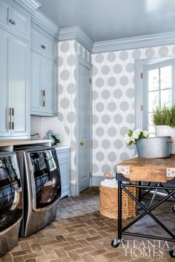A graphic Scion wallcovering adds a dose of whimsy to the laundry room; the custom folding table was made from a large butcher block Gilbreath found in France.