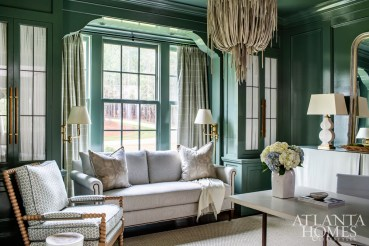 """Farrow & Ball's Green Smoke in high-gloss enriches the library's detailed millwork. Since the space also doubles as a home office, a skirted console and fabric-lined cabinetry keep """"work"""" components hidden."""