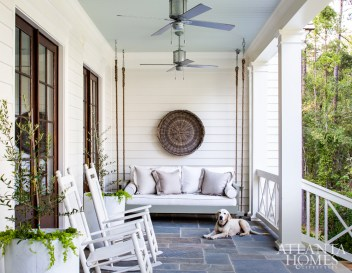 A custom bed swing on the back porch offers a serene spot for the family and their dog, Lexi, to enjoy views of the lake.