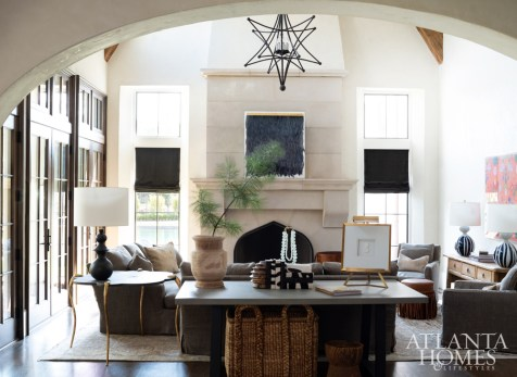 Architect Brad Wright incorporated dramatic details into the family room, where vaulted ceilings with reclaimed beams and steel doors take center stage. Designer Michele Johnson echoed the bold choices with overscale furniture and an iron chandelier by Solaria.