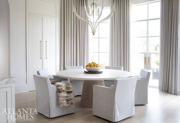 A custom concrete-topped table by Grey is surrounded by velvet slipcovered chairs from Restoration Hardware in the new breakfast room. The custom chandelier by Avrett and Rosemary Hallgarten alpaca linen drapery from Holland & Sherry are both through R Hughes.