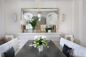 Channeled banquettes and end chairs upholstered in Sunbrella are by Bjork Studio. The custom furnishings continue with the charcoal-stained table with brass accents and sideboard with a smoky mirror top by Grey. The brass mirror and marble sconces are from Restoration Hardware.