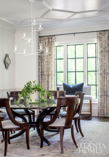 A white chandelier from Visual Comfort takes the otherwise traditional dining room in a more modern direction. The rug is from Moattar, and the draperies are from Holly Hunt.