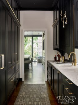 A contemporary pendant light from Ochre by R Hughes plays off of the brass hardware by Matthew Quinn Collection in the butler's pantry. The rug is Moattar, Ltd.