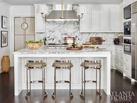 A custom swinging leather door designed by Burgess adds flair to the kitchen. The patent leather counter stools are from R Hughes.