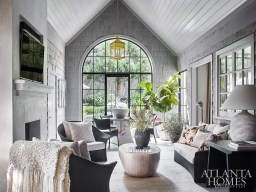 Architect D. Stanley Dixon transformed the home's screened porch, an addition made more than a decade ago, into an enclosed family room. The new arched iron window provides an improved visual connection to the backyard. The Pouf coffee table is Caste through R Hughes and the lantern is The Urban Electric Co.