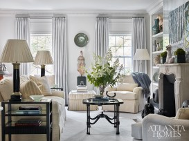 Greige-colored silk curtains from James Hare, a mirrored chimney breast, and walls, ceiling and trim painted Benjamin Moore's Revere Pewter all exude cool elegance in this living room.