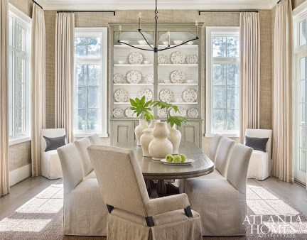 """The only room on the first floor defined by four walls (the other rooms follow a more open floor plan), the dining room is enveloped in a woven wallpaper by Phillip Jeffries. Webb chose unobtrusive linen draperies for the windows because """"the view is everything."""""""