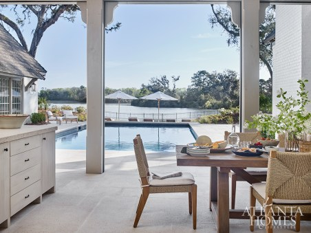 A pool, cabana and grilling porch are situated behind the house and close to the lake. The dining chairs, lounge chairs and chaises are from Logan Gardens.