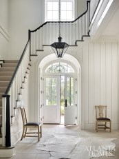 Atlanta architect Tim Adams and interior designer Beth Webb selected interior finishes for the Frederica residence, such as the limestone floor and wood paneling in the foyer.