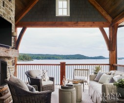 An outdoor sofa and chairs, all from Logan Gardens, invite lakeside conversations on one of the home's covered porches. The stools with nailhead trim are Lee Industries.