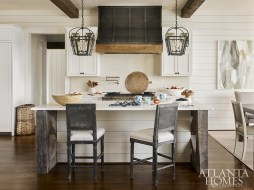 A pair of iron lanterns illuminate the kitchen island, which has a custom x-base made of reclaimed wood that's topped with marble counters. The barstools are by Bungalow 5 through JDouglas.