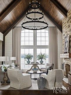 A tall stone fireplace with a reclaimed wood mantel creates a dramatic focal point for a tailored sofa and swivel chairs in the formal living room. The coffee table and console are from Tritter Feefer.